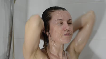 Young charming sexy girl shampoos her head in the bathroom Stock mozgókép
