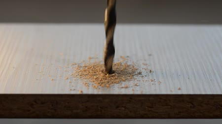 transmitir : The master drills a wooden plate with a drill