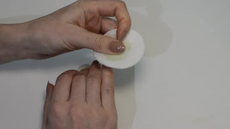Woman removes old nail polish with a cotton pad, doing hand manicure 動画素材