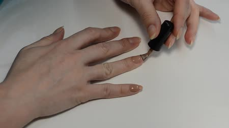 procedimento : Woman paints nails with beige nail polish while doing manicure Stock Footage