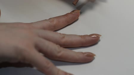 Woman paints nails with beige nail polish while doing manicure Stock Footage