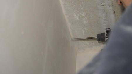 Worker drills a concrete wall with a long drill of a perforator