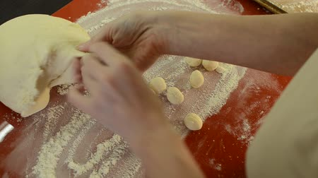 испечь : Woman cook sculpts round balls of dough from flour