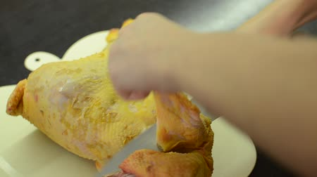 Chef cuts raw chicken with a knife