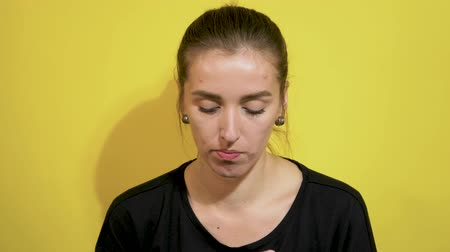 пятна : girl with acne on her face opens a candy and eat it on a yellow background