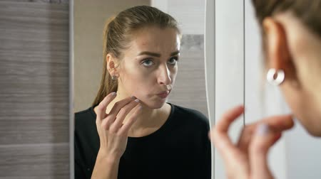 пятна : girl at the mirror, squeezes a pimple through pain.