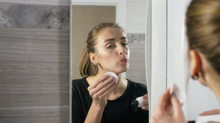 пятна : in the bathroom, the girl at the mirror apply lotion with the help of cotton sponges on her face and acne and pimps Стоковые видеозаписи