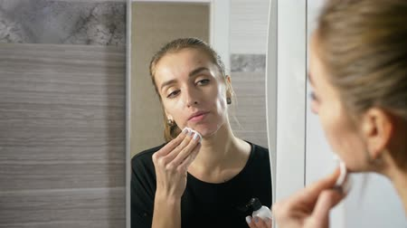 пятна : the girl at the mirror with the help of a wadded disk and applied lotion wipes acne from her face. the effect of the agent is visible instantly. Стоковые видеозаписи