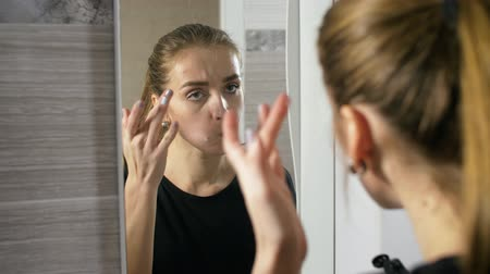пятна : in the bathroom the girl at the mirror apply lotion on her face and acne and pimps