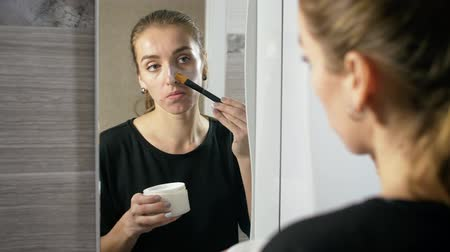 пятна : girl in the bath near the mirror with a brush, apply a cosmetic mask for the face.
