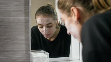 expressão facial : the girl in the bath near the mirror, washing her face, washes away the cosmetic mask.