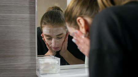 пятна : the girl in the bath near the mirror, washing her face, washes away the cosmetic mask.