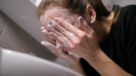 пятна : the girl in the bathroom washes rubbing soap in the face