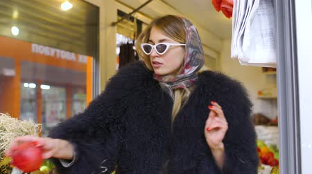 пятна : A girl in a modern style of clothes, in a fluffy cape, offers to buy red fruit from her