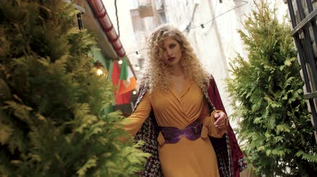 caramelo : a girl in a yellow dress, and curly hair with a red coat, walks along a narrow little street, with a wide, bright belt.