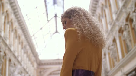 caramelo : a girl in a yellow dress and with a fat lilac belt and curly hair enters the frame looks into the camera and leaves