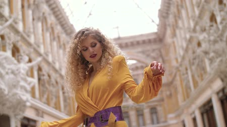 caramelo : a girl in a yellow dress and with a fat lilac belt and curly hair stands in against the background of the architecture in the passage, twist and pose for the camera