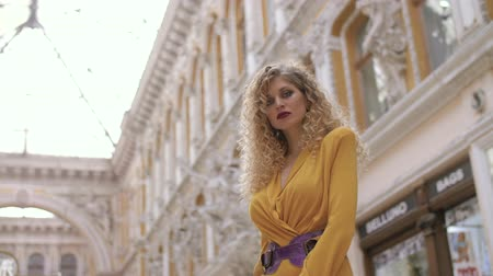 mustard : a girl in a yellow dress and with a fat lilac belt and curly hair stands in against the background of the architecture in the passageway, enter the frame and looks away