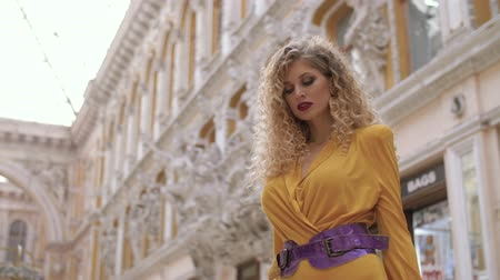 caramelo : a girl in a yellow dress and with a fat lilac belt and curly hair stands in against the background of the architecture in the passageway, looks into the camera and then unfolds and leaves