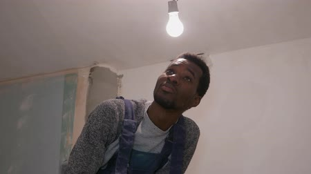 tél : a black guy works at a construction site, and rubs the ceiling with an emery cloth, looks at everything he did at his job, under the lamp