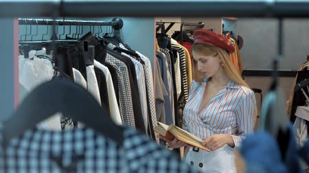 harcama : the girl in the red beret and white elegant skirt, stands in the clothing store, showroom, and reads a book Stok Video