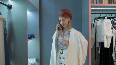 szál : girl in red beret white jacket in a striped shirt talking on the phone where she says something pleasant from what she smiles in the showroom. Stock mozgókép