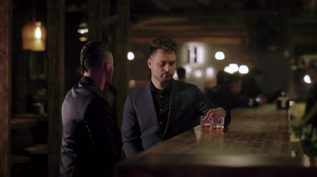 viski : two men in suits sit in the evening in a pub one looks at the other skeptically Stok Video