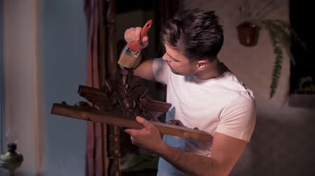 obnovit : A man with a brush at home works with a wooden carved crown for an antique wardrobe Dostupné videozáznamy