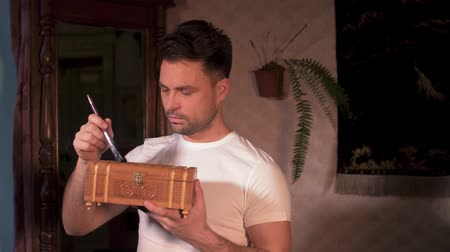 cabinetry : a man in a white shirt at home with a brush treats a wooden box a small chest Stock Footage
