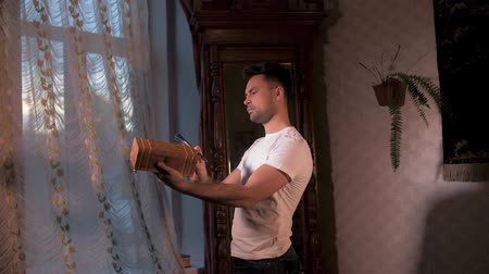 cabinetry : a man in a white shirt at home with a brush rubs the antique box against the background of an old antique mirror Stock Footage