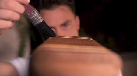 schrijnwerk : close-up, transition of focus from a wooden carved box to the eyes of a man who holds a brush over it