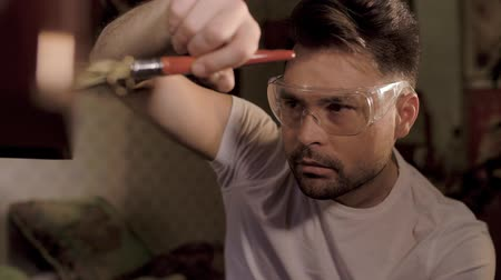 cabinetry : a man in a shirt and transparent glasses works with a brush on a lacquered table in which the key sticks out Stock Footage