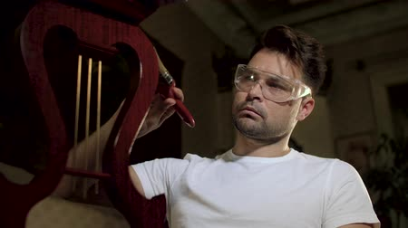 cabinetry : a man in a white shirt in transparent glasses for work wipes an antikaritny varnished furniture with a brush in the form of a harp