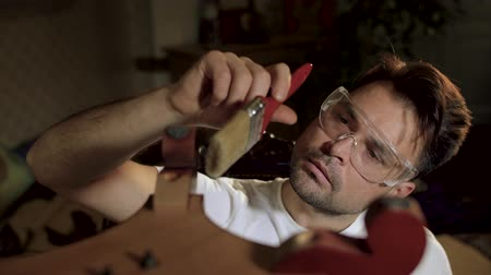 cabinetry : a man in a white shirt in transparent glasses for work wipes an antikaritny varnished furniture Stock Footage