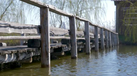 fishing pole : the atmosphere of calm and peace of water flashes on a wooden pier on the lake surrounded by reeds Stock Footage