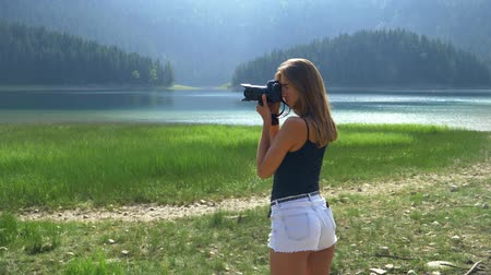 вертикально : tourist girl in white shorts photographs the lake first horizontally and then vertically Стоковые видеозаписи