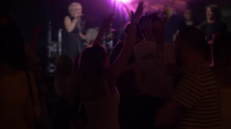 kabarık : people dance jumping at a concert in a nightclub on the background of the stage on which the music group Stok Video