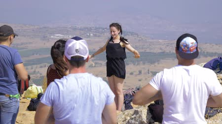juntar : Israel Mount Arbel - July 21, 2019. instructor on the mountain shows how to get up to a group of people to charge and squint from the bright sun of Israel