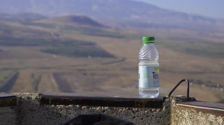 бронированный : Israel Golan Heights - July 21, 2019 a bottle of water from under the tea in the background, view from Golan Heights