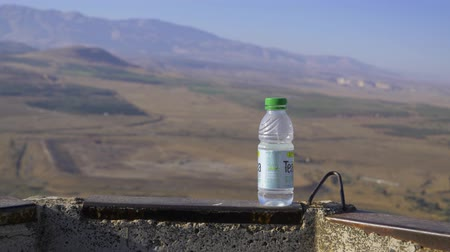kippur : Israel Golan Heights - July 21, 2019 a bottle of water from under the tea in the background, a view from Golan Heights which a female hand takes and takes