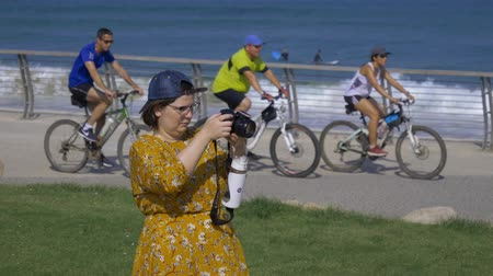 capturados : Israel Tel Aviv - July 21, 2019 woman in a yellow dress takes pictures with a camera Vídeos