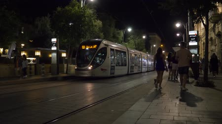 pont : Israel Jerusalem - July 21, 2019 there is a tram in jerusalem at night and people walk around Stock Footage
