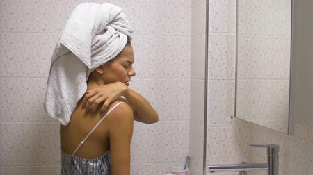 psoriasis : the girl in the bathroom itches redness on the skin with a towel on her head Stock Footage