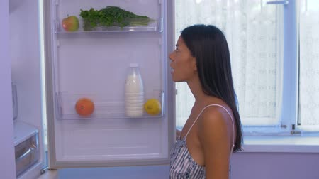 mrazák : the woman opens and looks in the refrigerator, but finding nothing useful, spreads her arms and shrugs, looks at the camera and makes a grimace