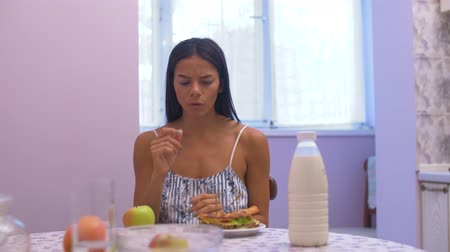 ambition : girl sits at a table in the kitchen and makes a choice between healthy and unhealthy food and then shrugs at the camera