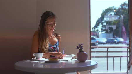 geçen : a girl sits at a window in a cafe writes to a notebook and then looks right out the window Stok Video