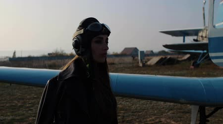 girl pilot in a special hat and leather jacket walks past the blades of the plane