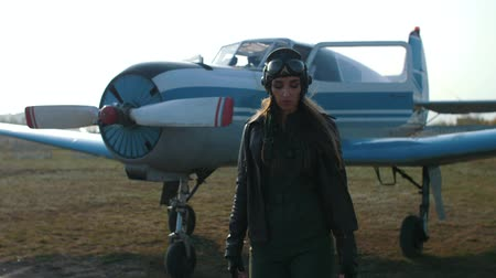 the pilot girl in a special headdress, on which glasses, and in a leather jacket, departs from the plane, comes to the fore and listens to the walkie-talkie, while looking at the camera