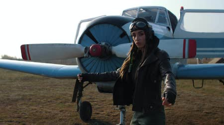 a female pilot enters the frame, throws a leather jacket on the background of the plane, looks at the camera and then looks around