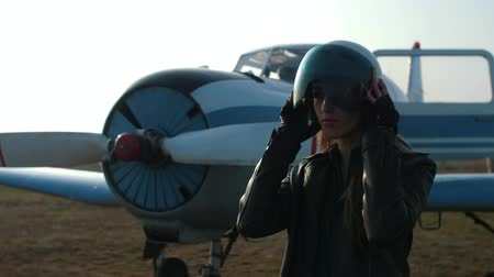 close-up of a girl against the background of an airplane who puts on a pilots helmet and looks away